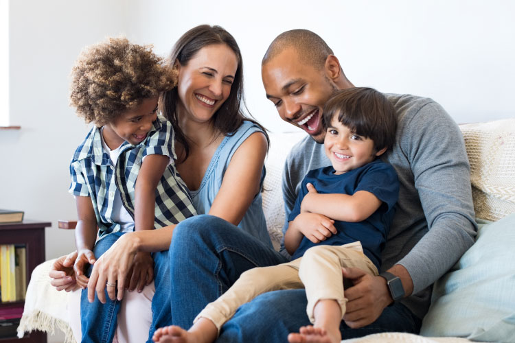 Multiracial family of a mom, dad, and two son smiling and laughing as they sit together on a couch