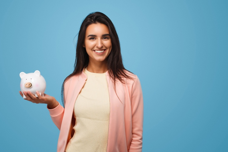 Brunette woman holds a piggy bank against a blue wall while wearing a pink cardigan