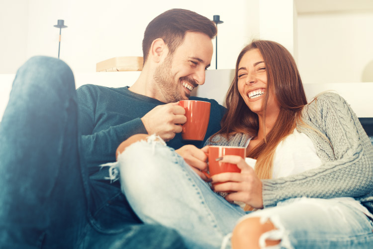 Brunette husband and wife drinking from mugs smile with their dental crowns while sitting on a couch
