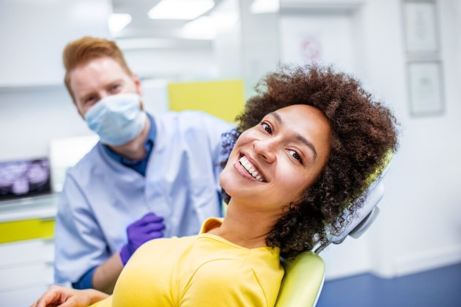 Curly-haired woman in a yellow shirt smiles while sitting in a dental chair in Portland, OR