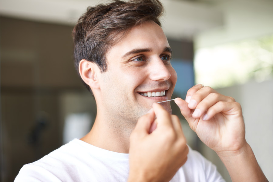 Brunette man smiles as he flosses because he understands it is important for his oral health