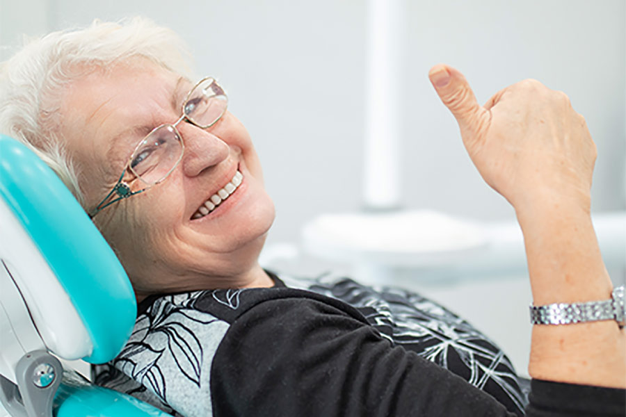 senior woman gives a thumbs up in the dental chair after a successful oral cancer screening